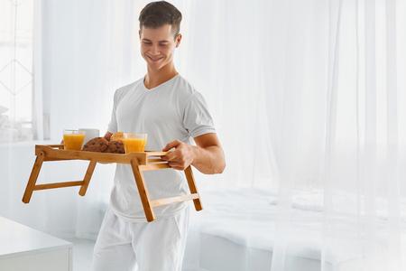 petit dejeuner romantique: Beau jeune homme avec petit d�jeuner romantique au lit