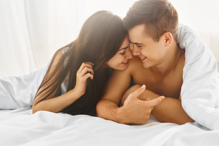 Close up portrait of romantic young man and woman in bed at home