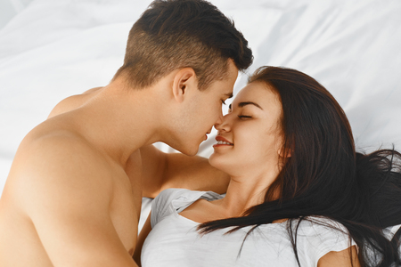 Close up portrait of a young romantic couple hugging and kissing, laying down on a white bed and loving each other. Love and relationships lifestyle, interior bedroom.