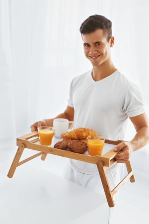 desayuno romantico: Hombre hermoso joven con romántico desayuno en la cama. Fondo blanco.