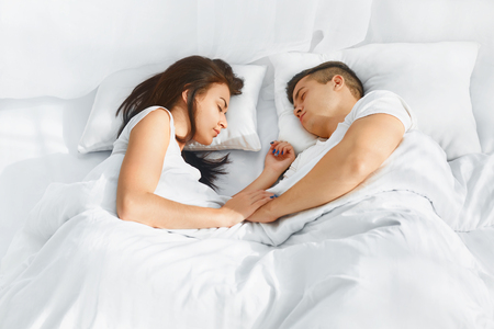 comfortable: Portrait of young lovely couple sleeping in the bed on white blankets faced to each other. Healthy lifestyle. Relationships , closeness. Healthy lifestyle. Wellness concept