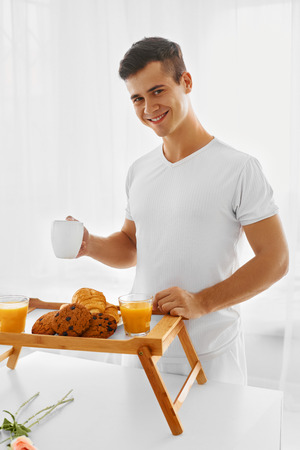 pyjama: Young handsome loving man in pyjama making romantic breakfast in the morning. Man putting orange juice, croissant, cookies and coffee on the bed tray decorating it with roses. White background. Valentines day or birthday. Stock Photo