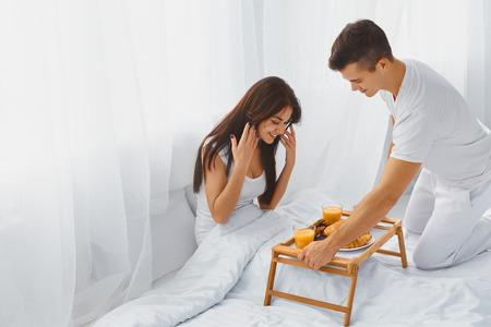 pareja en casa: Masculino sonriente hermoso sorprendiendo a su atractiva feliz femenino romántico desayuno en la cama por la mañana. Las relaciones, el cuidado, el concepto de amor.