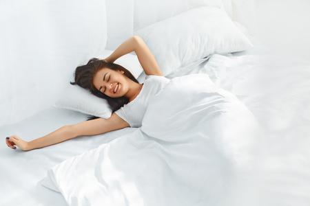 若い美しい女性の完全に休んだ彼女のベッドで目を覚ます。女性をスリープ解除後ベッドでストレッチします。健康的なライフ スタイル。ウェルネ