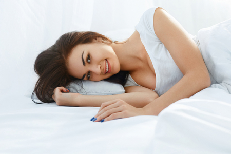 rested: Young beautiful smiling woman lying in her bed  fully rested after wake up
