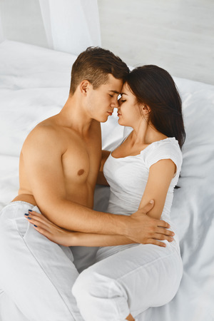 enamorados besandose: Close up portrait of a young romantic man and woman hugging and kissing, laying down on a white bed and loving each other