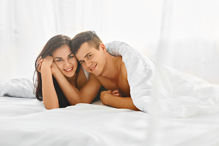 amantes en la cama: Young lovely tender couple enjoying morning lying in bed in their bedroom Foto de archivo