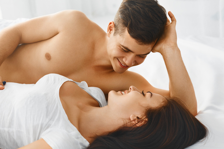 women kissing women: Close up portrait of a young romantic couple hugging and kissing, laying down on a white bed and loving each other Stock Photo