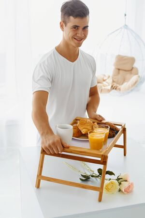 day bed: Portrait of young handsome man holding bed tray with romantic healthy breakfast for his woman