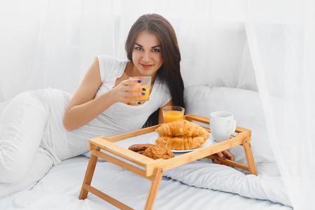 mujer en la cama: Mujer hermosa joven que come el desayuno en la cama y sonriendo a la cámara en la mañana Foto de archivo