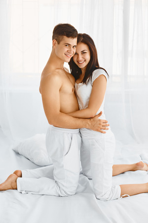 parejas amor: Sonriendo joven feliz abrazando pareja en la cama