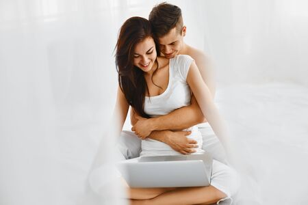 Happy young attractive couple hugging and looking at laptop photo