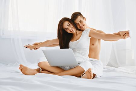 Smiling young couple having fun while sitting with laptop on the bed photo