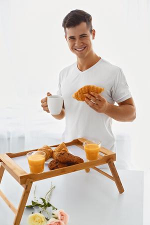 desayuno romantico: hombre cari�oso guapo joven que hace rom�ntico desayuno en la ma�ana Foto de archivo