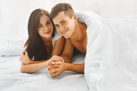 young man smiling: Young happy beautiful couple lying in bed and smiling at camera Stock Photo