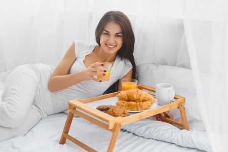 Young beautiful woman eating breakfast in bed and smiling at camera photo