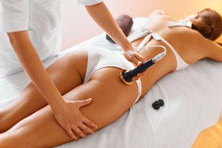 cuerpo femenino: Cuidado corporal. Ultrasonido cavitación Tratamiento Contorno Corporal. Mujer que consigue la terapia anti-celulitis y anti-grasa en las nalgas apretadas en salón de belleza. Tratamiento de spa. Wellness, Bienestar, Salud, Estilo de vida. Foto de archivo