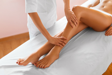 procedures: Woman Legs. Body Care. Beautiful Woman Getting Leg Massage Treatment In Spa Salon. Skin Care, Wellbeing, Wellness, Lifestyle, Relaxing Procedure. Stock Photo