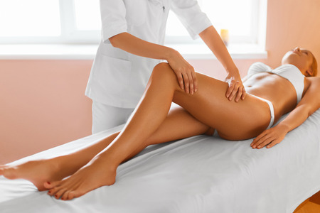 adult's feet: Woman Legs. Body Care. Beautiful Woman Getting Leg Massage Treatment In Spa Salon. Skin Care, Wellbeing, Wellness, Lifestyle, Relaxing Procedure. Stock Photo