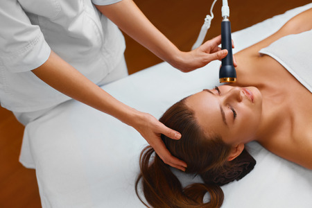 procedures: Face Skin Care. Beautiful Young Healthy Caucasian Woman Lies On A Table In A Medical Beauty Cosmetology Spa Salon Getting Facial Skin Care Treatment. Ultrasound Cavitation Anti-aging, Rejuvenation, Lifting Procedure. Beautician Applying Regenerative, Mois