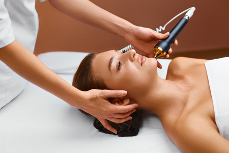 procedures: Face Skin Care Treatment. Ultrasound Cavitation Face Care Procedure In Medical Beauty Cosmetology Spa Center. Beautician Applying Regenerative, Rejuvenating, Moisturizing, Anti-aging Cosmetics On Skin Of Beautiful Young Healthy Caucasian Woman Using Ultra