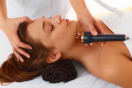 rejuvenating: Face Care Treatment. Ultrasound Cavitation Face Care Procedure In Medical Beauty Cosmetology Spa Center. Cosmetician Applying Regenerative, Rejuvenating, Moisturizing, Anti-aging Cosmetics On Skin Of Beautiful Young Healthy Caucasian Woman Using Ultrasoun Stock Photo