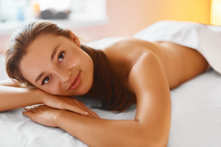 jeune fille: Spa Woman. Body Care. Massage Treatment, Skin Care, Wellness, Wellbeing Concept. Portrait Of Relaxed Beautiful Young Caucasian Woman Lying On The Massage Table, Smiling At Camera In Medical Cosmetology Spa Salon. Healthy Lifestyle Banque d'images