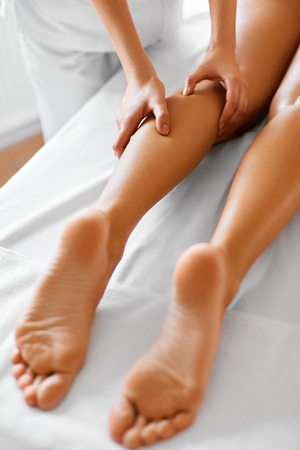 female legs: Spa Woman. Body Care. Close-up Of Beautiful Long Tanned Woman Legs Receiving Massage In Spa Salon. Body Care, Skin Care, Wellbeing, Wellness Concept. Anti-cellulite Spa Treatment. Stock Photo
