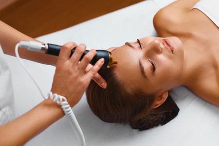 treatments: Face Skin Care Treatment. Ultrasound Cavitation Anti-aging, Rejuvenation, Lifting Procedure In Medical Beauty Cosmetology Spa Salon. Cosmetician Applying Regenerative, Moisturizing Cosmetics On Skin Of Beautiful Young Healthy Caucasian Woman. Tightening O Stock Photo