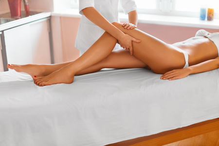 beautiful woman body: Spa Treatment. Body Care. Massage Of Human Legs In Spa Salon. Massaging Tired Muscles. Close-up Of Masseur Applying Moisturizing Oil And Massaging Beautiful Long Tanned Female Legs. Skin Care, Wellbeing, Wellness Concept. Anti-cellulite Massage. Stock Photo