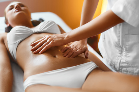 massage: Spa Woman. Body Care. Masseur Doing Massage On Relaxed Beautiful Young Caucasian Woman Body In The Spa Salon. Skin Care, Wellness, Wellbeing, Beauty Treatment Concept. Stock Photo