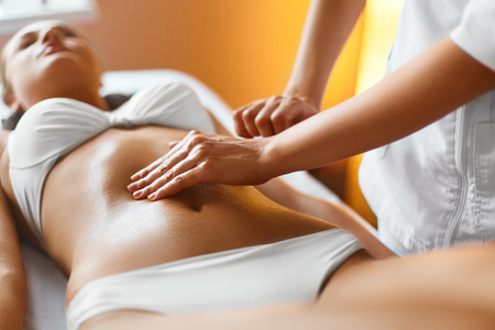 Spa Woman. Body Care. Masseur Doing Massage On Relaxed Beautiful Young Caucasian Woman Body In The Spa Salon. Skin Care, Wellness, Wellbeing, Beauty Treatment Concept. Stock Photo