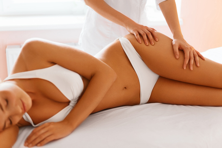 procedures: Body Care. Spa Massage Treatment. Close-up Of Beautiful Young Healthy Caucasian Woman Getting Anti-cellulite Massaging Procedure. Body Contouring Treatment. Body Care, Skin Care, Wellbeing, Wellness Concept.