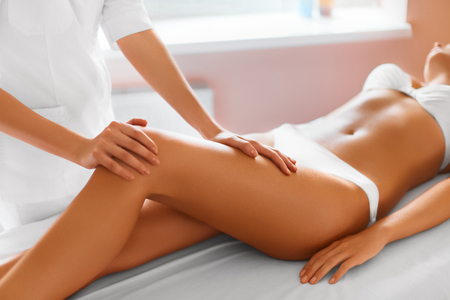 girl care: Spa Woman. Close-up Of Sexy Woman Getting Spa Treatment. Leg Massage Therapy In Spa Salon. Masseur Applying Moisturizing Oil And Massaging Beautiful Long Tanned Female Legs. Body Care, Skin Care, Wellbeing, Wellness Concept.