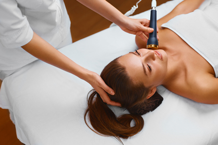 treatments: Face Skin Care. Beautiful Young Healthy Caucasian Woman Lies On A Table In A Medical Beauty Cosmetology Spa Salon Getting Facial Skin Care Treatment. Ultrasound Cavitation Anti-aging, Rejuvenation, Lifting Procedure. Beautician Applying Regenerative, Mois