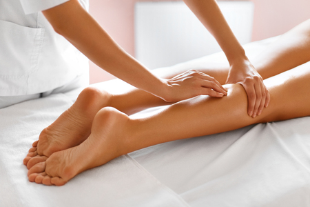 massager: Spa Woman. Close-up Of Sexy Woman Getting Spa Treatment. Leg Massage Therapy In Spa Salon. Masseur Applying Moisturizing Oil And Massaging Beautiful Long Tanned Female Legs. Body Care, Skin Care, Wellbeing, Wellness Concept.