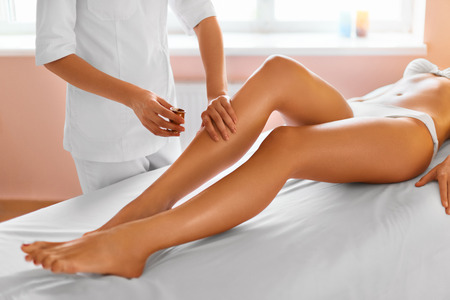 Body Care. Spa Treatment. Leg Massage Therapy In Spa Salon. Massaging Tired Muscles. Close-up Of Masseur Applying Moisturizing Oil And Massaging Beautiful Long Tanned Female Legs. Skin Care, Wellbeing, Wellness Concept. Anti-cellulite Massage. Stock Photo