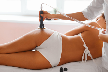 wellness: Body Care. Ultrasound Cavitation Body Contouring Treatment. Woman Getting Anti-cellulite And Anti-fat Therapy On Her Tight Buttocks In Beauty Salon. Spa Treatment. Wellness, Wellbeing, Healthcare, Lifestyle.