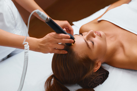 beauty spa: Face Skin Care. Beautiful Young Healthy Caucasian Woman Lies On A Table In A Medical Beauty Cosmetology Spa Salon Getting Facial Skin Care Treatment. Ultrasound Cavitation Anti-aging, Rejuvenation, Lifting Procedure. Beautician Applying Regenerative, Mois