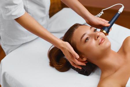 esthetic: Face Skin Care. Beautiful Young Healthy Caucasian Woman Lies On A Table In A Medical Beauty Cosmetology Spa Salon Getting Facial Skin Care Treatment. Ultrasound Cavitation Anti-aging, Rejuvenation, Lifting Procedure. Beautician Applying Regenerative, Mois