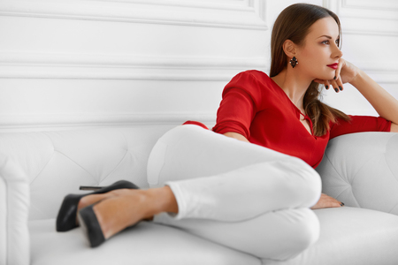 woman in office: Elegant Woman. Fashionable Beautiful Successful Business Lady Relaxing On Stylish Sofa. Wellbeing, Luxury Lifestyle. Interior, Furniture. Stock Photo