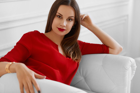 mooie vrouwen: Elegant Woman. Fashionable Beautiful Successful Business Lady Relaxing On Stylish Sofa. Wellbeing, Luxury Lifestyle. Interior, Furniture. Stockfoto