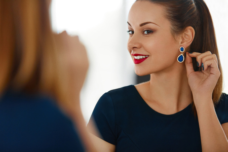 earings: Fashion Woman Portrait. Beautiful Elegant Successful Female With Evening Make-up Wearing Luxurious Blue Dress Smiling In The Mirror. Jewelry And Beauty. Wellbeing, Luxury Lifestyle.
