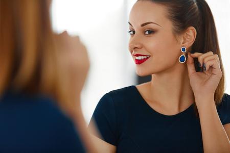 caras emociones: Retrato de la mujer de la moda. Hermosa Mujer Exitosa elegante con maquillaje de la tarde desgasta la alineada azul de lujo sonriente en el espejo. Joyería y belleza. Bienestar, estilo de vida de lujo.