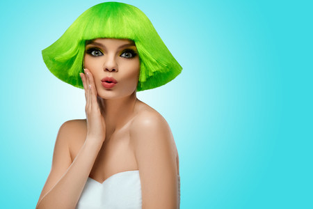 wig: Woman Hair. Fashion Stylish Beauty Portrait With Green Hair. Beautiful Girls Face Close-up. Haircut. Hairstyle. Fringe. Professional Makeup. Make-up. Vogue Style Woman. Against blue background