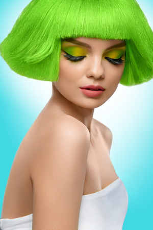 hair model: Beauty Fashion Model. Beautiful Woman With Short Green Hair And Luxury Professional Makeup. Haircut. Fringe Hairstyle. High Quality Image. Against blue background
