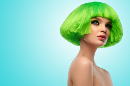 short haircut: Woman Hair. Fashion Stylish Beauty Portrait With Green Hair. Beautiful Girls Face Close-up. Haircut. Hairstyle. Fringe. Professional Makeup. Make-up. Vogue Style Woman. Against blue background
