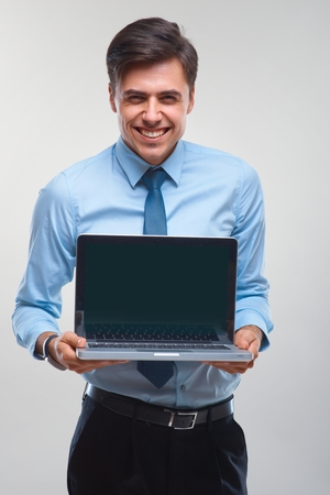 laptop stand: Business man holding a laptop against a white background
