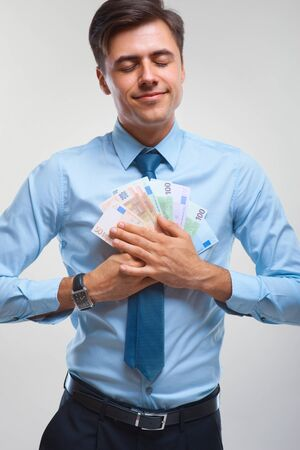 business finance: Businessman celebrating money income against white background