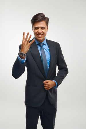 number four: Closeup of a young business man showing showing four number. Stock Photo